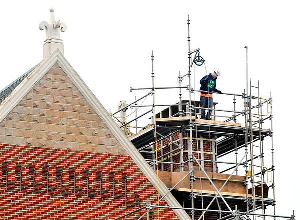 John P. Cleary |  The Herald Bulletin<br /> Tyler Whitehead, of Wells Masonry, Indianapolis, works high on the scaffolding around the chimney of St. Mary's Catholic Church as they do tuck pointing around the structure Wednesday afternoon.