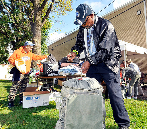 John P. Cleary |  The Herald Bulletin<br /> Air Force veteran Michael Boykin, of Muncie, secures his duffle bag after packing it with clothing and handouts received at the 2017 Madison County Veterans Stand Down event as Army veteran Steve Johnson, left, goes down the line picking out some clothing items Friday.