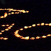 Mark Maynard | for The Herald Bulletin<br /> A Raven and the number 100 made of luminaries marked Anderson University's Centennial Homecoming on Friday night.