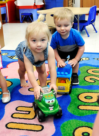 John P. Cleary    The Herald Bulletin<br /> Violet Jones and Keagan Box drive their toy trucks around the room as they play in Elwood Elementary School's 16-29 month ols pre-K classroom this past week.