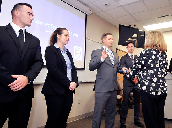 John P. Cleary    The Herald Bulletin<br /> Anderson City Clerk Shelia Ashley, right, administers the oath of office to new Anderson Police officer Andrew Lanane as the other new officers, Adam Watters, left, Courtney Skinner, and Sean Brady look on during a swearing-in ceremony at APD headquarters Friday morning.
