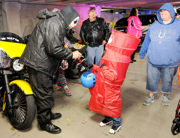 Don Knight   The Herald Bulletin<br /> Dressed as an inflatable fan man, Jackson Gumm, 5, gets candy from Max Johnson who is wearing a scary clown mask during APD's Trunk or Treat on Friday. Johnson was volunteering with the group Second Chance To Get It Right. The event was moved into APD's parking garage due to the rain.