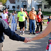Don Knight | The Herald Bulletin<br /> Participants in the Reconciliation March joins hands for a prayer after walking across the Eisenhower Bridge on Saturday.
