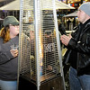 Don Knight | The Herald Bulletin<br /> From left, Marsha Miller, Janice Miller and Jeremy Miller from Elkhart Ind. warm up around a heater before the start of Breeders Crown races at Hoosier Park on Friday.
