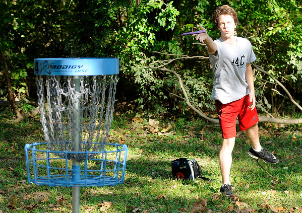 Don Knight | The Herald Bulletin<br /> Carson Wallace aims for the basket on the 4th hole while playing the Sanders Memorial Disc Golf Course at Edgewater Park on Wednesday. Signs marking the holes still need to be installed after which there will be an official opening. You can find more information and updates about the course on the Sanders Memorial Disc Golf Course Facebook page.