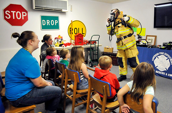 John P. Cleary |  The Herald Bulletin<br /> Children from Gateway Association listen to Anderson Fire Department Deputy Chief Wilbert Kelly as gives a fire safety program to them at the department's Fire Safety House located in the Anderson Public Library.
