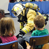 John P. Cleary |  The Herald Bulletin<br /> Anderson Fire Department Deputy Chief Wilbert Kelly gives a fire safety program to children from Gateway Association showing them how firefighters look and sound in their protective gear, and how they search for persons in a fire. The children were at AFD's Fire Safety House located in the Anderson Public Library for a fire safety program.