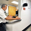 John P. Cleary |  The Herald Bulletin<br /> Madison County Sheriff Scott Mellinger shows where they could install a full body scanner in the hallway with the controls and monitor behind the counter in the book-in area of the jail.