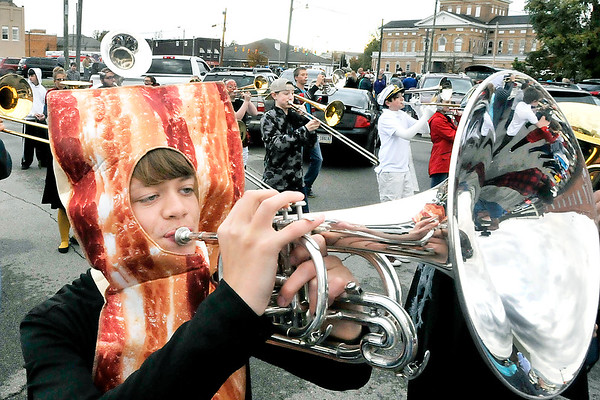 John P. Cleary |  The Herald Bulletin<br /> Elwood High School ninth grade band member Brandon Alfrey plays his horn through his costume as the band leads the Elwood Halloween parade through the street of downtown Monday evening.