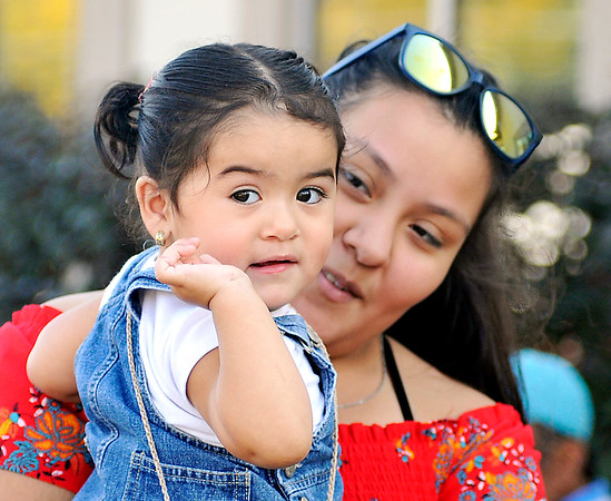 John P. Cleary    The Herald Bulletin<br /> Consuelo Roman, 13, holds her niece, Yetzale Pachec, 1, as she waves at people attending the Hispanic Heritage Festival.