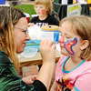 Don Knight | The Herald Bulletin<br /> Sarah Roudebush, 7, sits still as Amber Pulis paints a butterfly on her face during Socktoberfest at Dickmann Town Center on Saturday. Pulis was volunteering with the Libertarian Party at the event.