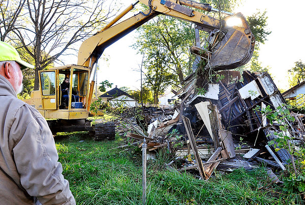 John P. Cleary    The Herald Bulletin<br /> Workers from Fredericks Inc. demolish this vacant house in the 2200 block of Locust Street Tuesday morning. There were three houses earmarked for demolition in this block as part of the city's Blight Elimination Program.