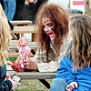 Mark Maynard | for The Herald Bulletin<br /> A demented fugitive from Brickmore Asylum, played by Tina McDole of Anderson, offers to share her bloody baby doll with these visitors to Indy Scream Park.