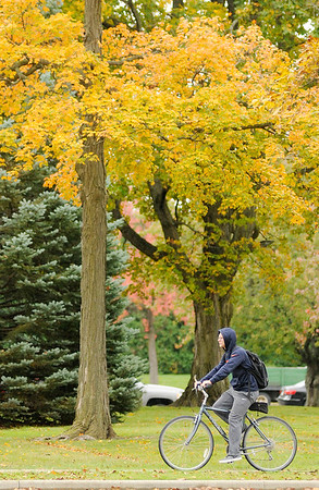 Don Knight | The Herald Bulletin<br /> A student rides a bike on the sidewalk next to 5th Street at Anderson University on Monday. After sunny skies and warm temperatures last week this week is forecast to feel more like fall with the arrival of a cold front on Monday.