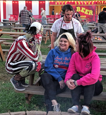 Mark Maynard | for The Herald Bulletin<br /> These visitors to Indy Scream Park's Midway have attracted a very creepy clown and a murderous butcher to keep them company.