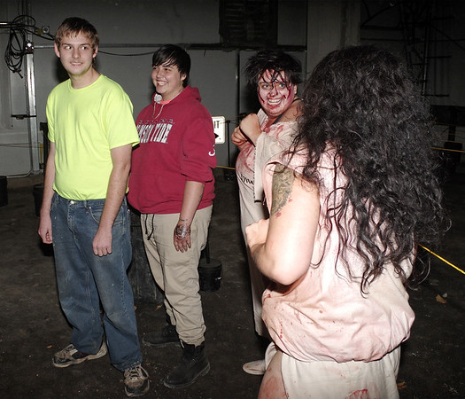 Mark Maynard | for The Herald Bulletin<br /> An Indy Scream Park visitor appears a bit apprehensive about entering the Brickmore Insane Asylum after he encounters these crazed inmates who managed to sneak out.