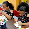 Don Knight | The Herald Bulletin<br /> From left, twins Laniyah and Shaniyah Miller, 10, decorate their masks during Family Fun Day at the Anderson Museum of Art on Saturday.