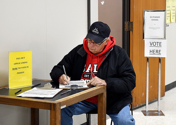 John P. Cleary   The Herald Bulletin<br /> Early voting at the Madison County Government Center. Voter fill out their voter application form before casting their ballot.