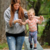 John P. Cleary | The Herald Bulletin<br /> Kayla Davenport helps her daughter Aria, 20 months old, keep her balance as she walks along a ledge in Falls Park Wednesday. The Davenports live in Pendleton and  were enjoying the last summer-like day as the temperatures are forecast to fall to below-normal levels for the weekend.