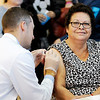 Don Knight | The Herald Bulletin<br /> Zach Tyrcha from Walgreens gives Maria Tovar Ramirez and flu shot during Keith Trent's Coats of Caring at the Anderson High School on Saturday.