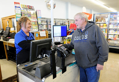 Don Knight | The Herald Bulletin Harvest Market assistant manager Char Tinch rings up a Mega Millions ticket purchase for Herb Hollenback on Thursday. Tinch has noticed increased demand for Mega Millions tickets as the jackpot is over $900 million for Friday's drawing.