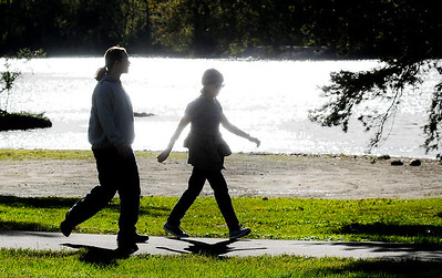 Don Knight | The Herald Bulletin Walkers are silhouetted by the suns reflection off the lake at Shadyside Park on Tuesday. The National Weather Service is forecasting temperatures in the 50s for the rest of the week and a chance of rain on Friday.