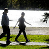 Don Knight | The Herald Bulletin<br /> Walkers are silhouetted by the suns reflection off the lake at Shadyside Park on Tuesday. The National Weather Service is forecasting temperatures in the 50s for the rest of the week and a chance of rain on Friday.