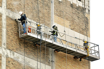 John P. Cleary | The Herald Bulletin Crews work high in the air Monday as they do brick work on the south face of the Tower Apartment building which is being refurbished.