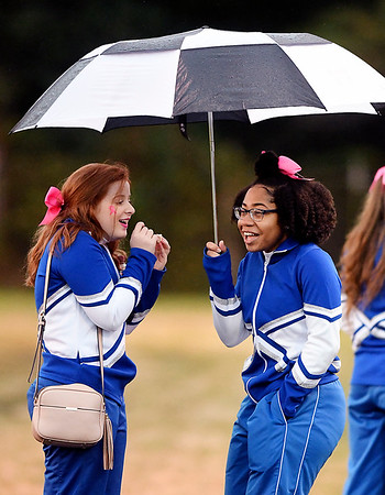 John P. Cleary | The Herald Bulletin<br /> These Anderson Preparatory Academy cheerleaders share a laugh and an umbrella before the start of their football game against Wes-Del Friday evening.