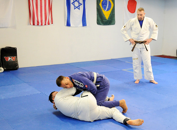 Don Knight   For The Herald Bulletin<br /> Brazilian Jui jitsu instructor Andrew Newkirk looks on as John Jarrett and Joel Heffelfinger practice a move during their class at the YMCA on Saturday.