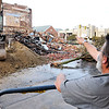 John P. Cleary | The Herald Bulletin<br /> Work started Monday on the demolition of the historic building at Harrison and Washington Streets in Alexandria which had started to collapse. Here Alexandria resident Arthur Campbell points out some of the detail he can see on the interior wall now that it is exposed.