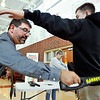 John P. Cleary | The Herald Bulletin<br /> Anderson High School assistant principal Brad Milleman uses a metal detector on students as they enter the building as part of their school safety while school staff member Missy Morris, background, checks their back backs.