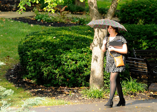 Don Knight | The Herald Bulletin<br /> A student walks through the valley at Anderson University as the sun shines through the clouds after a brief heavy downpour on Tuesday. Rain is in the forecast through the rest of the work week.