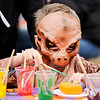 Don Knight | The Herald Bulletin<br /> Camden Muniz paints a pumpkin while dressed as a T-Rex during Pumpkin Palooza at Anderson High School on Saturday.