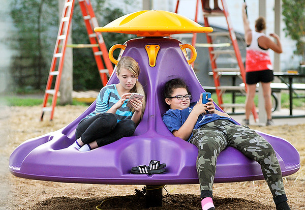 John P. Cleary | The Herald Bulletin<br /> Neighborhood kids enjoy the renovated Horne Park at 7th & John Street after the city refurbished it with new playground equipment, shelter house, and picnic tables. Here Madison Fetty, 13, and Elisabeth Flores, 14, find this new playground piece a comfortable place to relax and catch up with their smart phones.