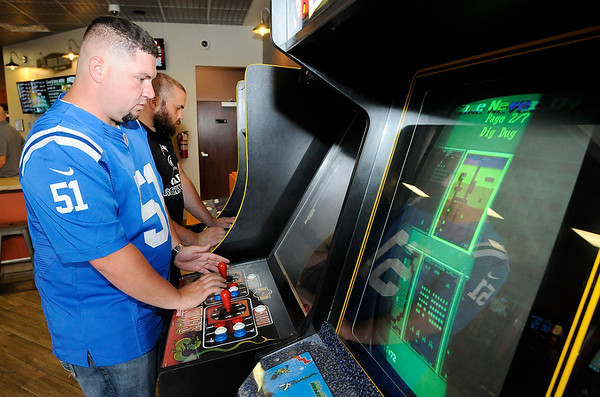 Don Knight | The Herald Bulletin<br /> From left, Eddie Kissane and Jason Barker play Mortal Combat II and Pac Man during Digital District's grand opening on Thursday. The bar in the former Diggidy's location has video, board and card games. In addition to craft beer on tap they have a full coffee bar, craft sodas and a light menu.