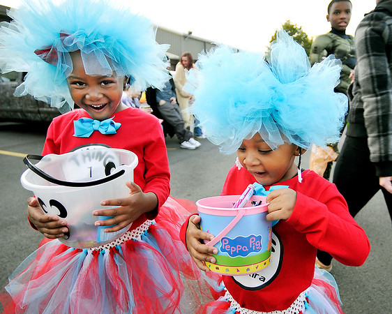 John P. Cleary   The Herald Bulletin<br /> Tiaris Johnson, 4, and Tiy Aira Walton, 3, get excited as they check out their bucket of goodies they've gotten at the neighborhood Trunk-or-Treat event Monday evening at the Geater Center.