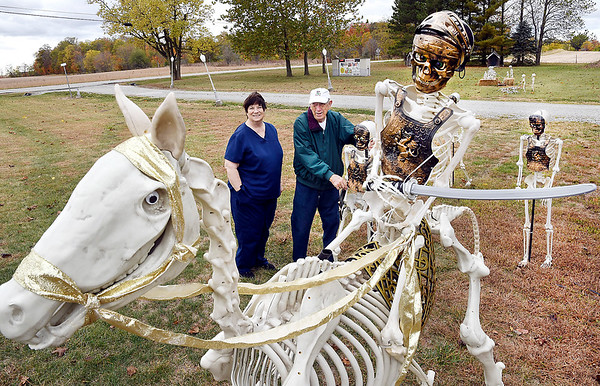 Gail and Lloyd Shinholt with their Roman horseback and foot soldiers display that is part of their large Halloween skeleton display.