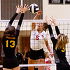 Frankton's Kate Sperry drives the ball across the net as Alexandria's Ashlynn Duckworth and McKenzie Adams work to block.