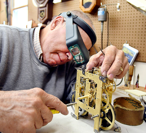 Joe Remington works on this clock mechanism at the Alexandria Clock Shop where he has been building and repairing clocks for 40 years.