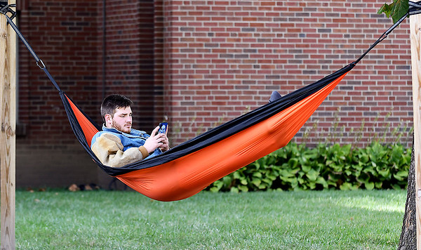 Brayden Nelson, a Anderson University freshman from Remus, Michigan, checks his phone as he enjoys the pleasant afternoon relaxing in his hammock behind Rice Hall on the Anderson University campus Thursday afternoon.