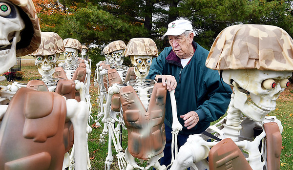 Lloyd Shinholt inspects his platoon of skeleton soldiers he has as part of his large skeleton Halloween display between Edgewood and Lapel.