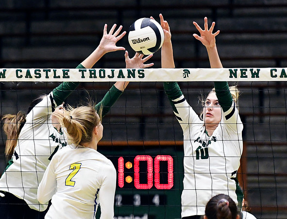 Pendleton's Aubree Dwiggins and Gracie King have their hands up to block Greenfield-Central's Molly Schwarzkopf's kill attempt.