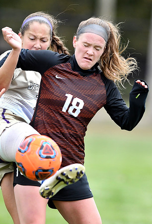 Defiance's Jordan Furko tries to kick the ball around the body of Emily Buchman, of Anderson University, as Buchman tries to block Furko off the ball.