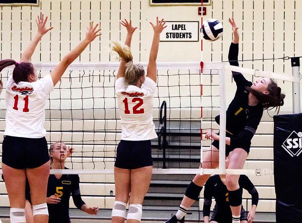 Frankton's Gabby Carmack and Chloe Thomas work to block the ball as Alexandria's Katelyn Bait drives it over the net.