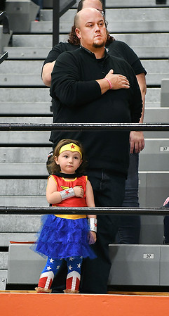 """Four year-old """"Wonder Woman"""" Lucy Hale salutes the American flag with her hand over her heart just like her father, Paul Hale of Daleville, during the playing of the National Anthem before the Anderson University volleyball match against Manchester Wednesday evening. It was senior night and they came to watch their cousin, Emily Hale, play her last home game as a senior."""