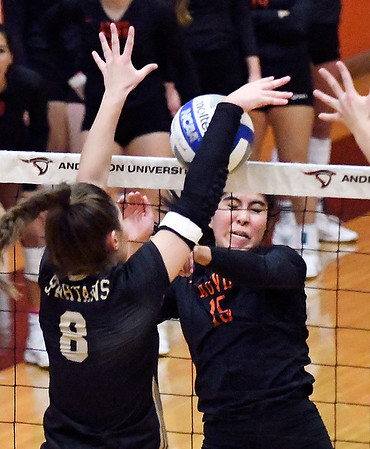 Manchester's Rachel Ressler blocks the ball on AU's Jimena Montano's kill attempt but the ball gets caught against the net and falls to the floor for an Raven point.