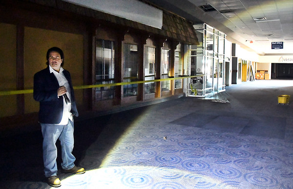 Mark Squillante, new owner of the Mounds Mall, walks through the building with a flashlight.
