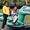 Kadence Cooley, 9, and her cousin Eirrion Bonner, 5, enjoy riding the dinosaur at the playground in Streaty Park Monday, having fun during spring break.