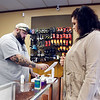 Aaron Goodson, the owner of Vintage Vapors, rings up a purchase for customer Danielle Clevenger in his north Anderson vape shop.